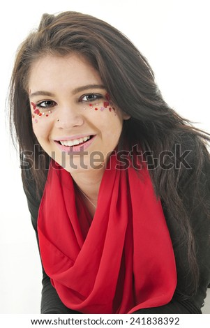 Close-up image of a beautiful teen girl with her face adorned with rhinestones and sparkly red hearts.  On a white background.   - stock photo