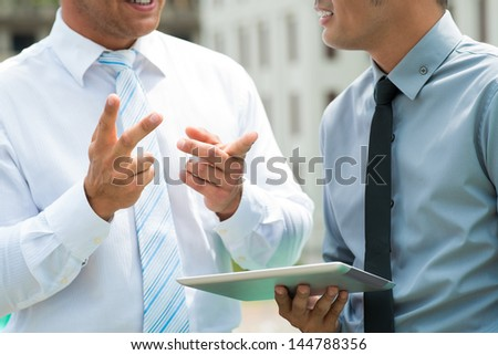 Close-up image of a business team sharing and discussing ideas with enthusiasm - stock photo
