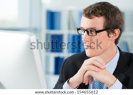 Close-up image of a businessman deeply concentrated at work on the foreground - stock photo