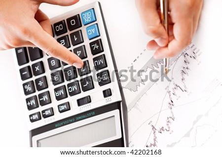 Close-up image of a businessman's hand analyzing stock charts