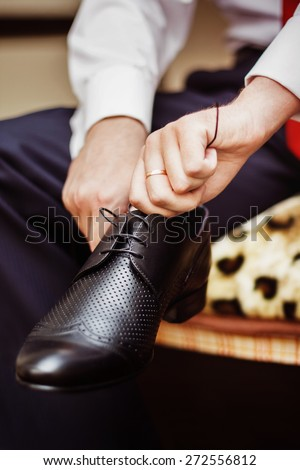 Close up image of a businessman who is preparing for his workday and tying a shoe lace.  - stock photo