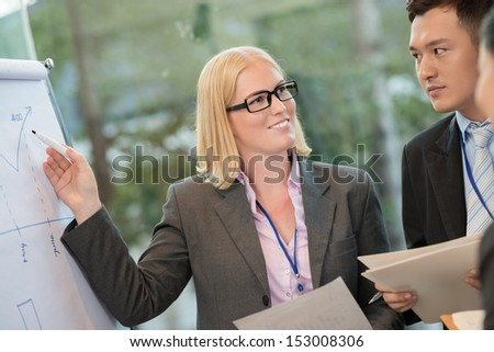 Close-up image of a ceo pointing at the data on the board while talking with her colleagues on the foreground  - stock photo