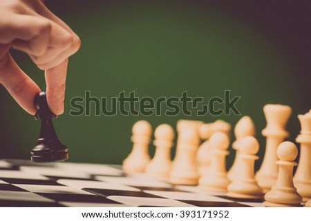 Close-up image of a chess board with chess pieces and a human hand.