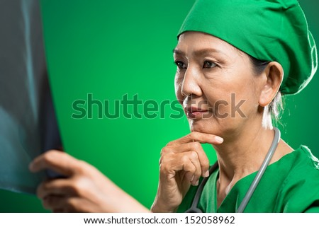 Close-up image of a contemplating senior doctor examining an x-ray on the foreground - stock photo