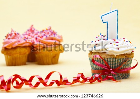 Close-up image of a cupcake with number 1 candle and red streamer while strawberry cupcake in background. - stock photo