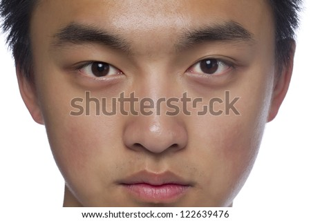 Close-up image of a face of teenager looking at the camera against the white surface - stock photo