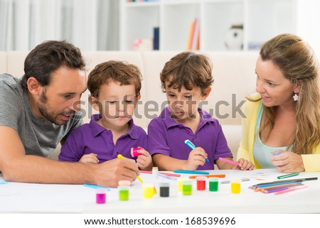 Close up image of a family painting together at home  - stock photo