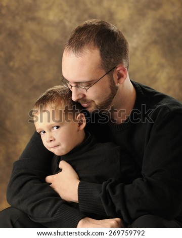 Close up image of a father snuggling with his young son who is grinning at the viewer from the corner of his eye.  Both are dressed in black. - stock photo