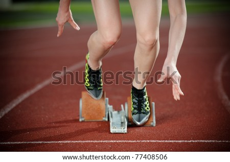 Close-up image of a female runner leaving the starting blocks for a sprint run on a track - stock photo
