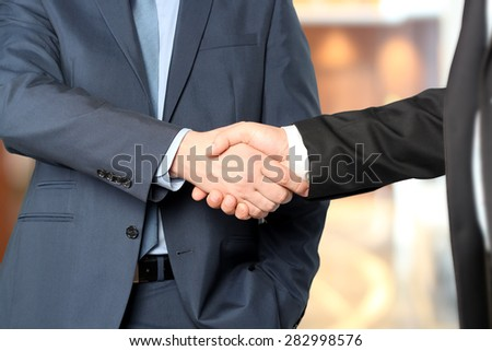 Close-up image of a firm handshake between two colleagues - stock photo