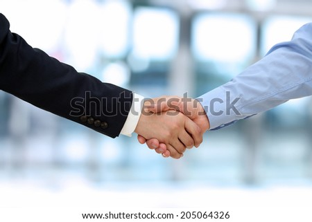 Close-up image of a firm handshake  between two colleagues in office. - stock photo