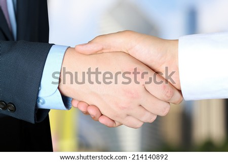 Close-up image of a firm handshake  between two colleagues outside - stock photo