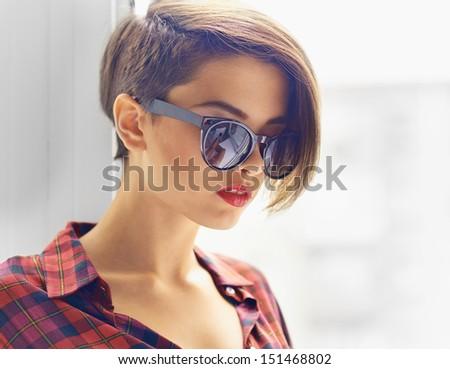 Close-up image of a gorgeous young woman wearing stylish sunglasses - stock photo