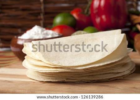 Close-up image of a group of empty tortilla shells with blurred vegetables on the background - stock photo