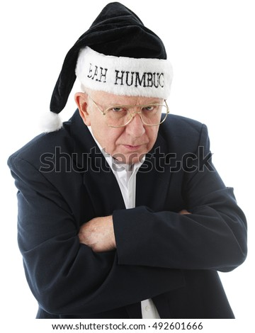 "Close-up image of a grumpy old man in black, wearing a black ""Bah Humbug"" Santa hat.  On a white background."