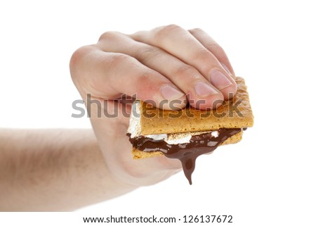Close-up image of a hand holding a melted smores sandwich over the white background - stock photo