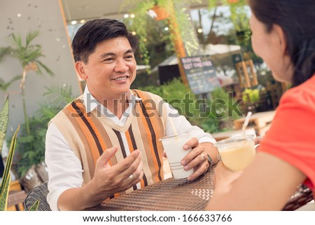 Close-up image of a handsome senior man with a cocktail at a cafe  - stock photo