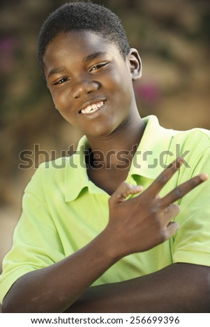 """Close-up image of a happy young Haitian teen boy gesturing """"victory"""" with his fingers.  Shallow DOF with focus on eyes. - stock photo"""