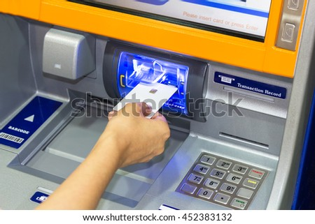 Close up image of a human hand inserting a debit chip card  in the ATM. Women hand businessman inserts credit card into the ATM and withdraws money
