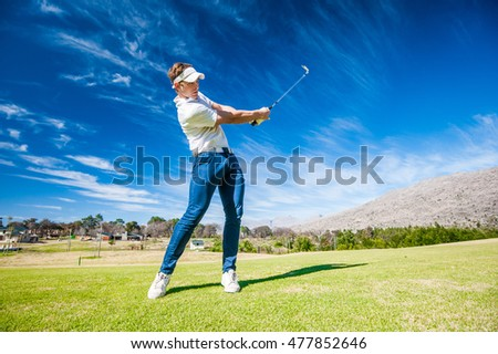 Close up image of a male golfer playing a shot on the fairway on a golf course in south africa