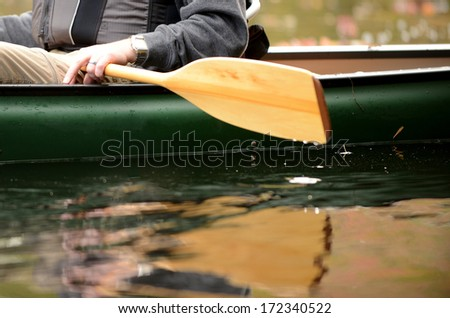 close-up image of a man on a river in a green canoe with a wooden paddle - stock photo