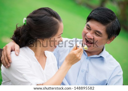 Close-up image of a mature couple, a woman feeding his man on the foreground - stock photo