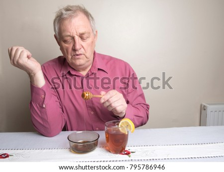 Close up image of a mature man putting honey into a glass of hot water and lemon