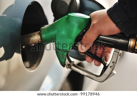 Close-up image of a mens hand refilling the car with a gas pump - stock photo