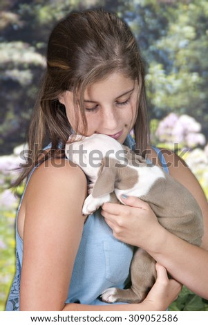 Close-up image of a pretty teen girl lovingly cuddling with her adorable sleeping puppy.  - stock photo