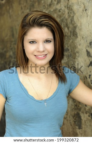 Close-up image of a pretty young teen by a rustic stone wall. - stock photo