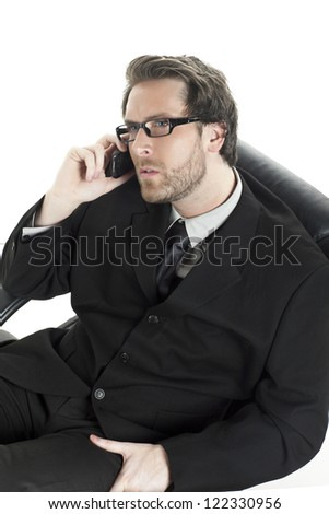 Close-up image of a relaxed businessman talking on the mobile phone while sitting on his office chair