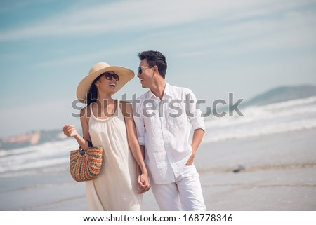 Close up image of a young glamorous couple walking together on the beach in the summertime  - stock photo