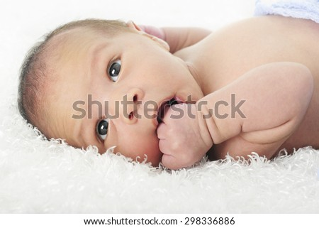 Close-up image of an alert newborn chewing on his fist.  On a white background. - stock photo