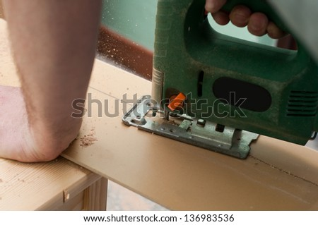 Close up image of an electric jigsaw cutting sheets on a wooden plank - stock photo