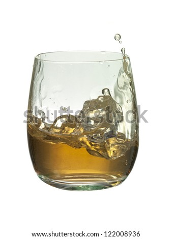 Close-up image of an ice cube into a glass on brandy creating a splash