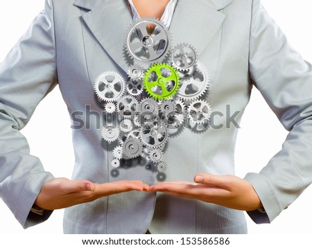 Close up image of businesswoman holding gears in hands - stock photo