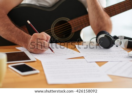Close-up image of composer examining sheets with notes - stock photo