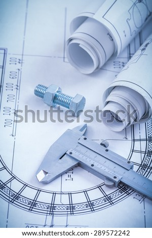 Close up image of construction drawings screw bolt with nut trammel caliper on blueprint architecture and building concept. - stock photo