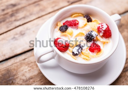 Close up image of corn flakes with berries and milk in white bowl on wood background. Healthy breakfast background