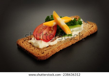 Close-up image of crackers with some cream tomato, cucumbers and cheese - stock photo