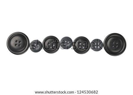 Close up image of different sizes of black cloth buttons against white background - stock photo