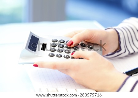 Close-up image of efficiency sales woman sitting at office and using calculator. Business people.  - stock photo