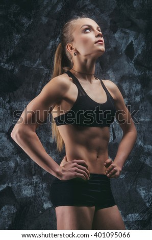 Close up image of female in sports clothing relaxing after workout on grey background. Muscular female body.