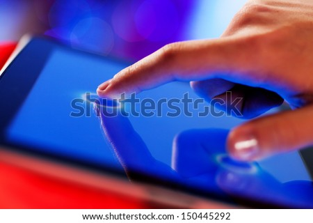 Close-up image of finger touching blue screen - stock photo