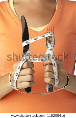 Close up image of hand holding utensils with tape measure - stock photo