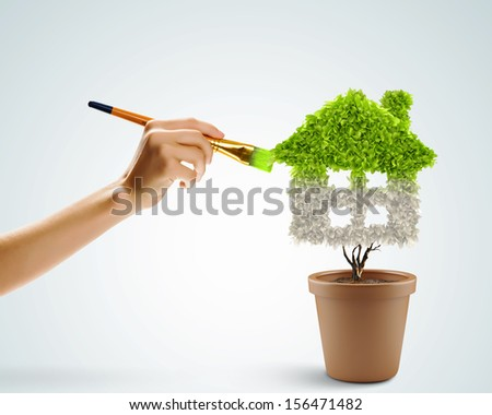 Close up image of hand painting plant shaped like house - stock photo