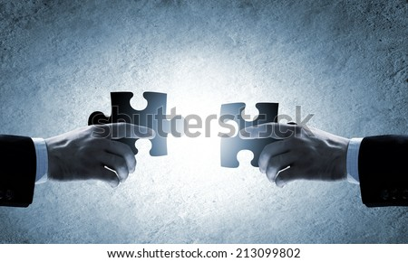 Close up image of hands connecting puzzle elements - stock photo