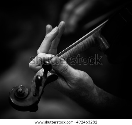 Close up image of hands playing a violin