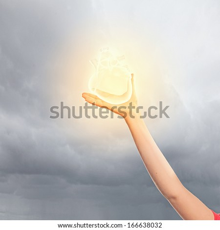 Close-up image of human hand holding heart - stock photo