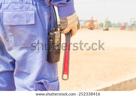 Close-up image of human hand holding wrench in well head oil and gas location - stock photo